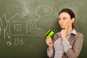 Closeup portrait of pretty young business woman against green board holding credit card and drawing beautiful house with backyard. Mortgage concept